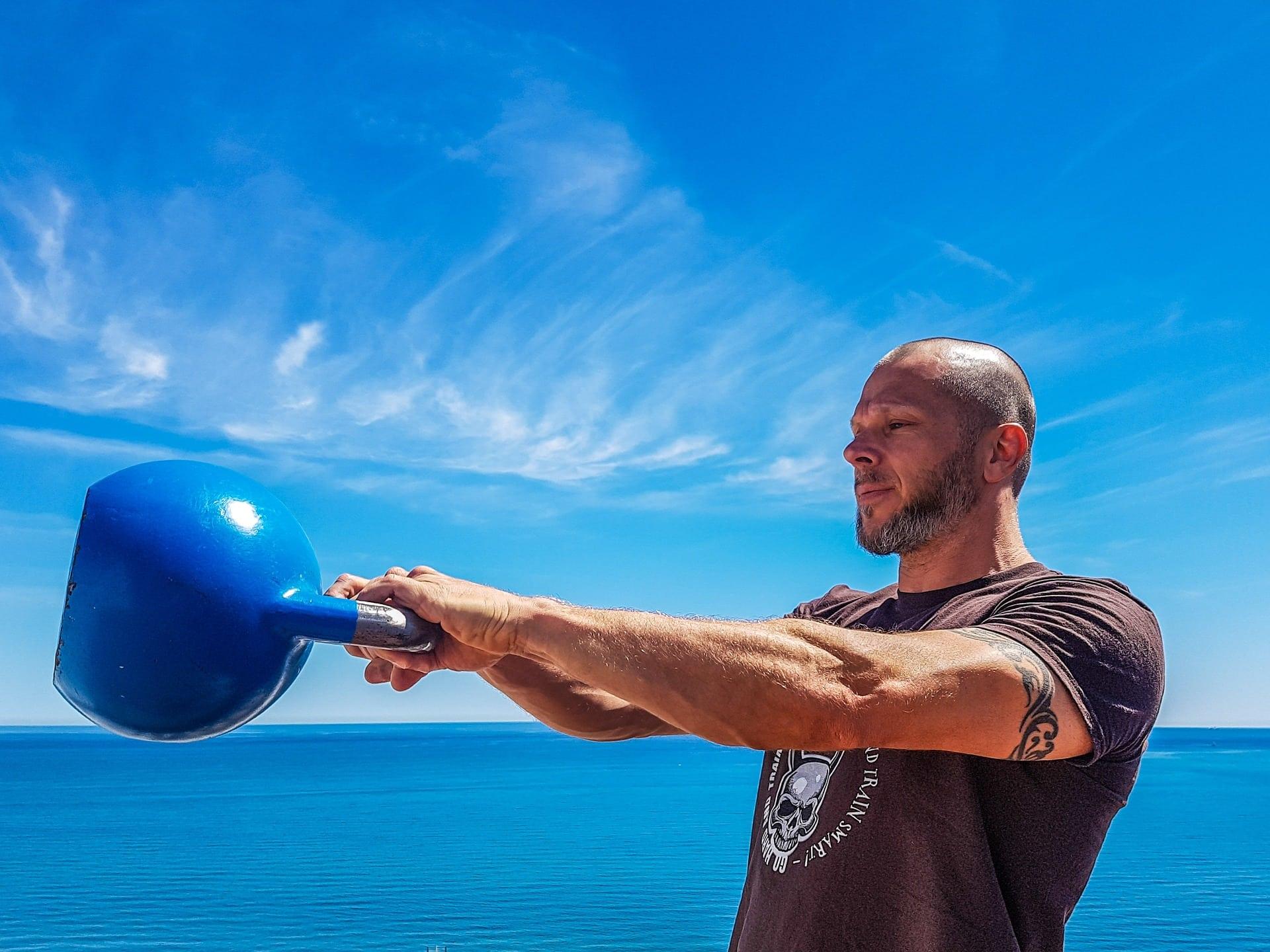 atleta che esegue esercizio swing con kettlebell