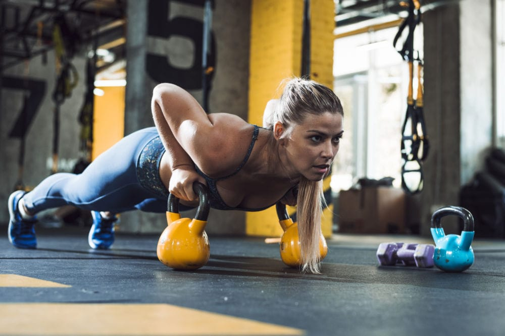 donna che esegue push up con kettlebells