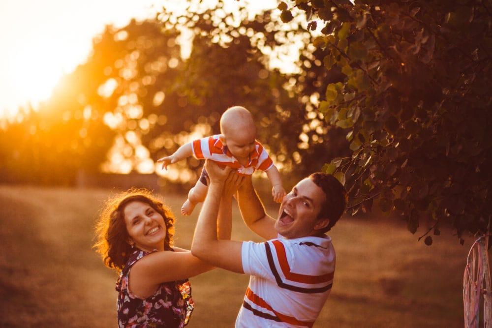 papà e mamma che sollevano al cielo il neonato