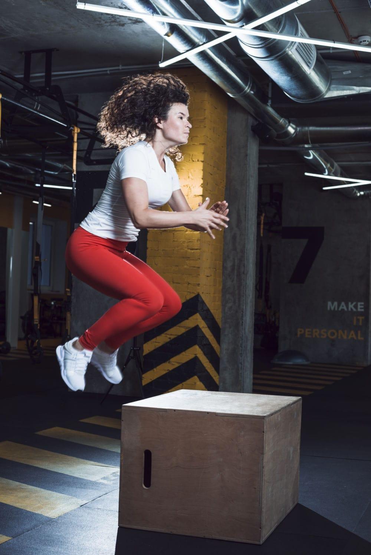 atleta che salta su un cubo
