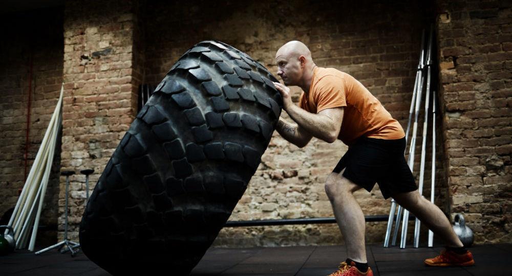 Atleta che sposta di forza una ruota grande