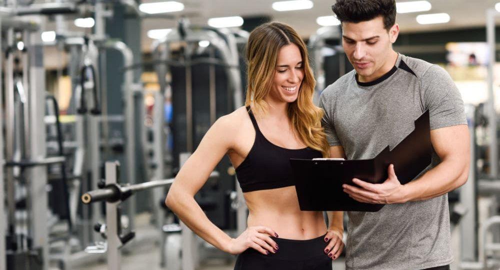 personal trainer che spiega la scheda di allenamento