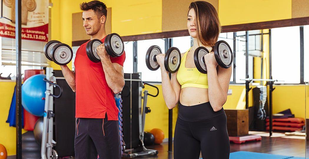 uomo e donna che allenano i bicipiti in sala pesi